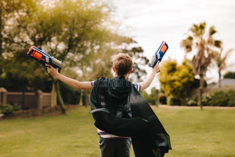 Pojke som låtsar för att vara superhero arkivfoto