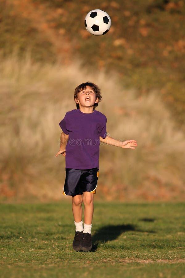 Pojke som leker med fotbollbollen i Fall fotografering för bildbyråer