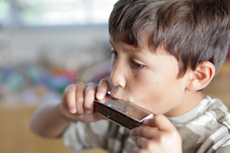 Pojke som leker med harmonicaen arkivfoto