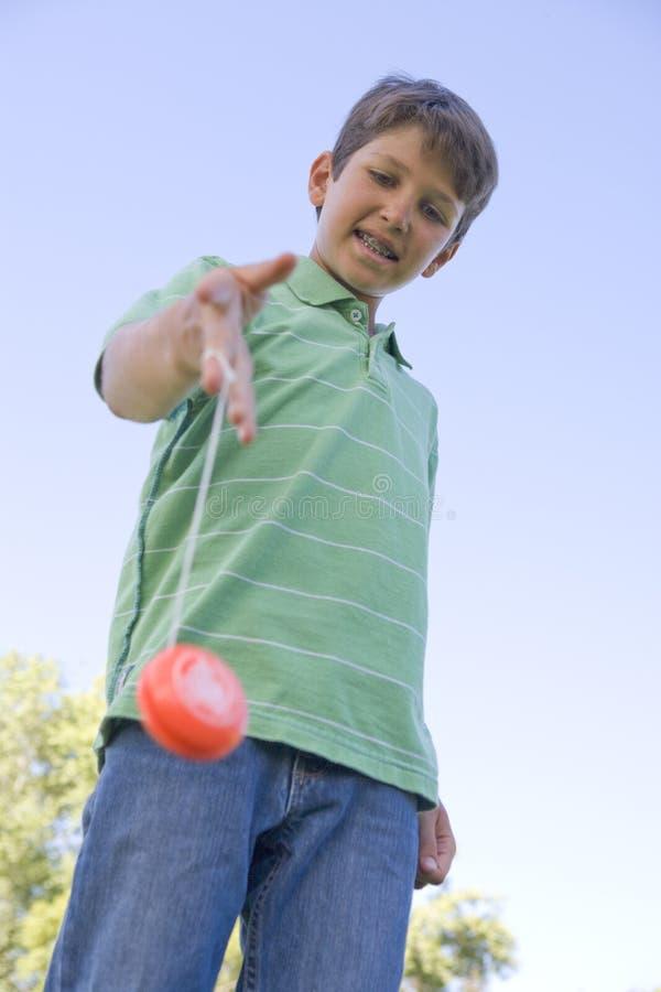 pojke som ler utomhus genom att använda yobarn royaltyfri bild