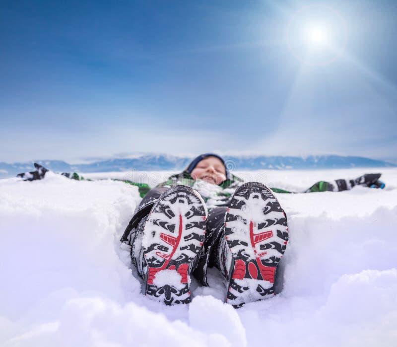 Pojke som ligger i djup snö på bergkullen royaltyfri foto