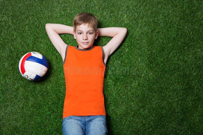 Pojke som ligger med bollen på grönt gräs royaltyfri fotografi