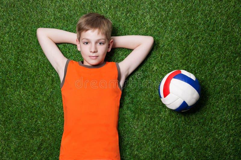 Pojke som ligger med bollen på slut för grönt gräs upp arkivfoto