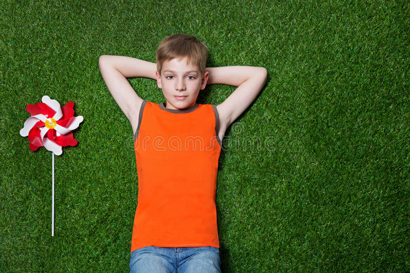 Pojke som ligger med lilla solen på grönt gräs fotografering för bildbyråer