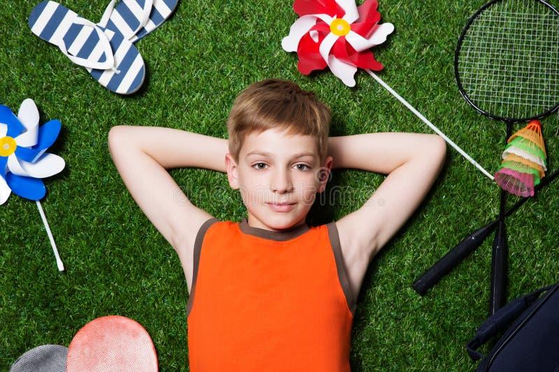 Pojke som ligger med sportutrustning på grässlut upp royaltyfri bild
