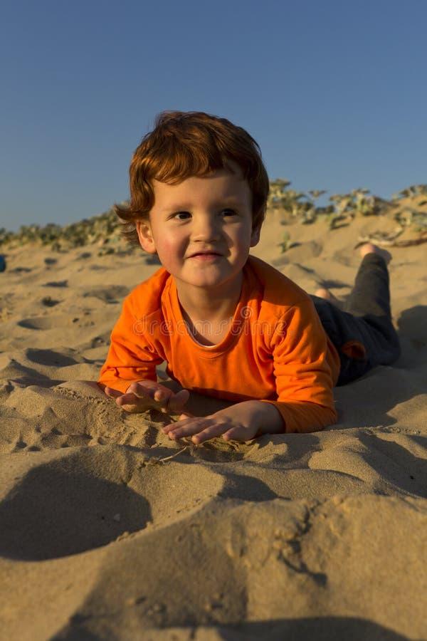 Pojke Som Ligger På Hans Mage På Stranden Arkivfoton