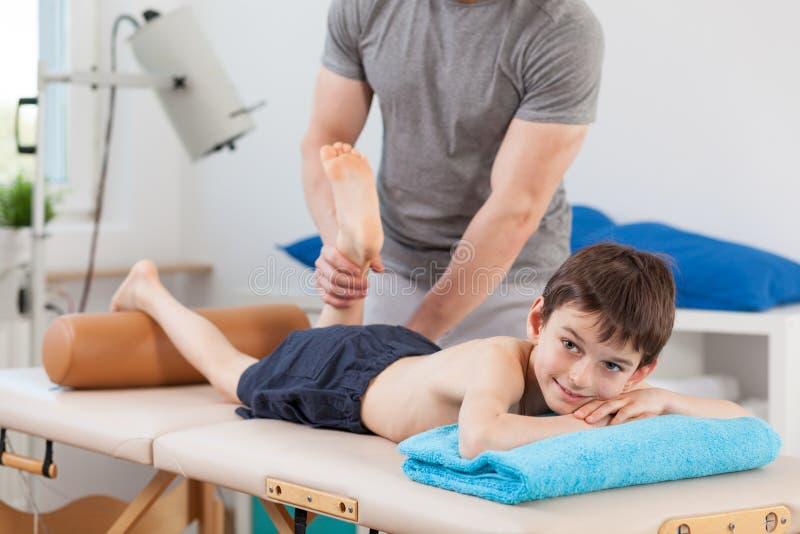 Pojke som ligger på sjukgymnastiktabellen royaltyfria foton