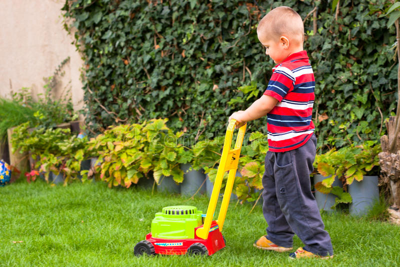 pojke som little arbeta i trädgården arkivbilder