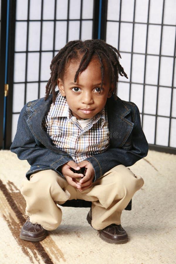 pojke som little huka sig ned fotografering för bildbyråer