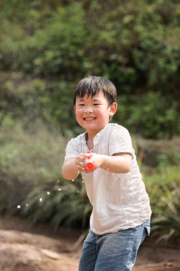 Pojke som lyckligt leker med en vattentryckspruta royaltyfria bilder