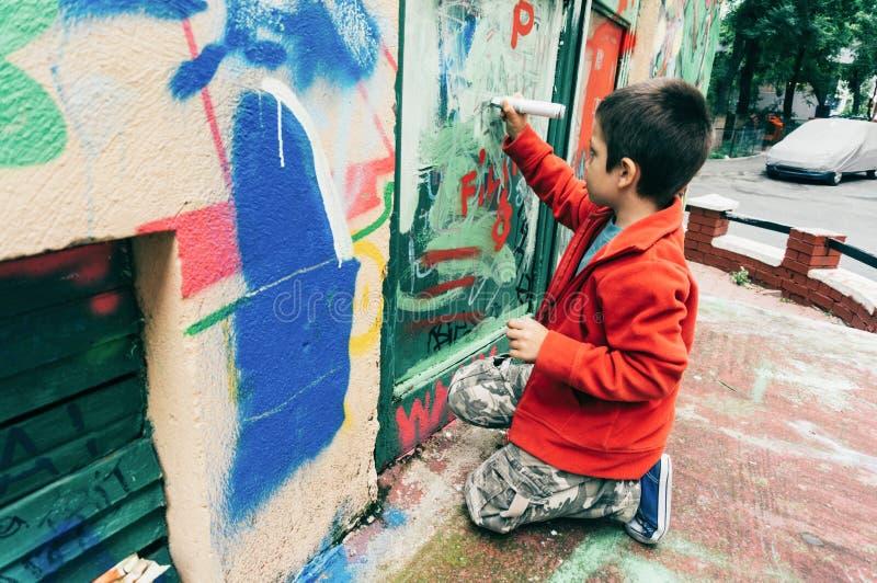 Pojke som märker väggen med grafitti royaltyfria foton