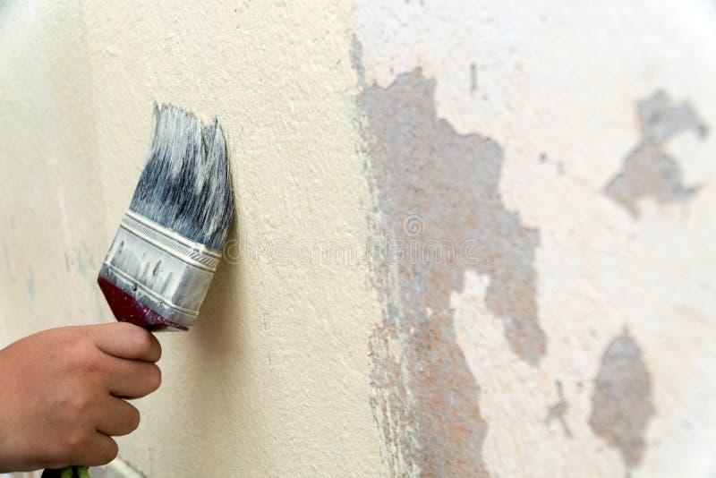 Pojke som målar den gamla husväggen arkivbild