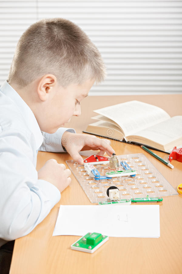 Pojke som monterar den elektriska strömkretsen arkivbild