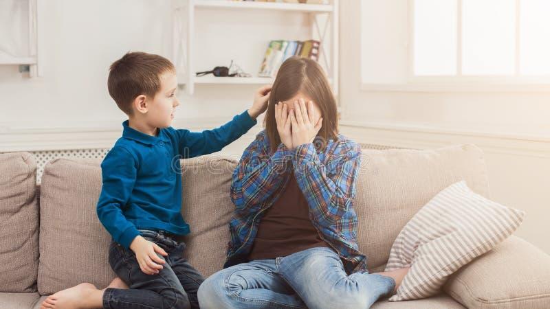 Pojke som ner hemma lugnar hans skriande syster royaltyfri foto