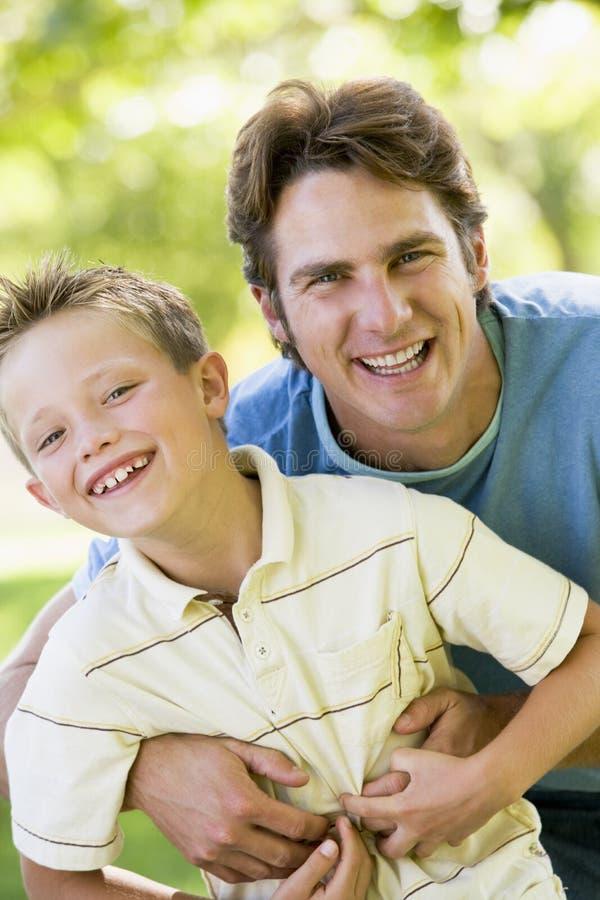 pojke som omfamnar mannen som ler utomhus barn royaltyfria bilder