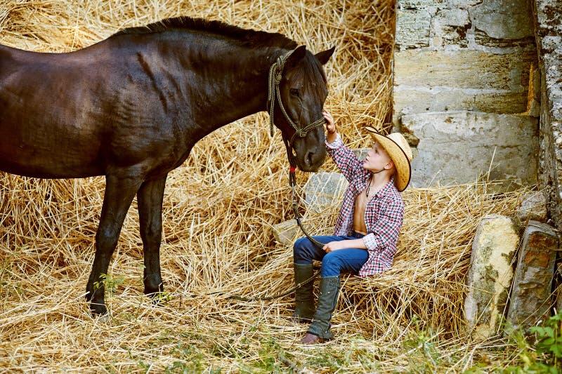 Pojke som poserar med en häst efter genomköraren ranch royaltyfri fotografi