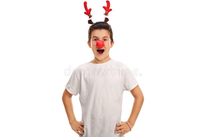 Pojke som poserar med röda horn på kronhjort och en röd näsa royaltyfria foton
