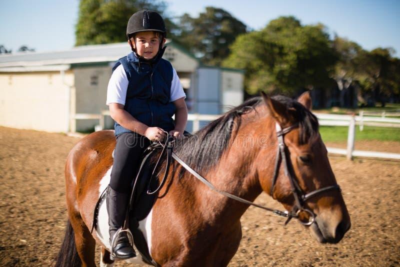Pojke som rider en häst i ranchen arkivfoto