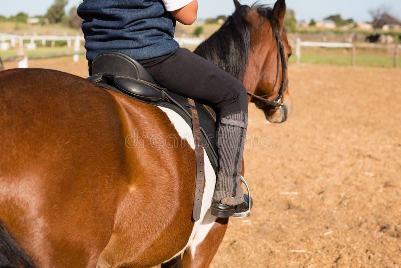 Pojke som rider en häst i ranchen arkivfoton