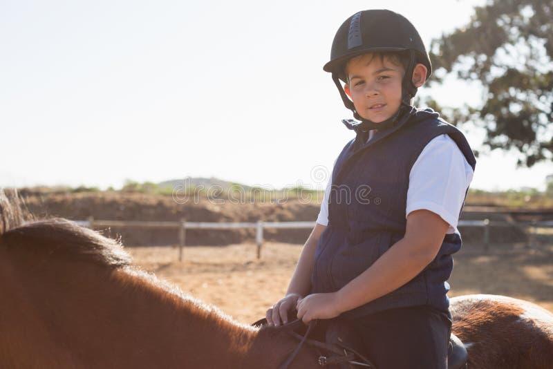 Pojke som rider en häst i ranchen royaltyfri fotografi