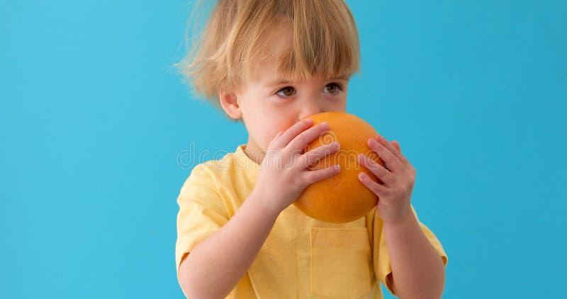 Pojke som rymmer en grapefrukt sund mat arkivbild