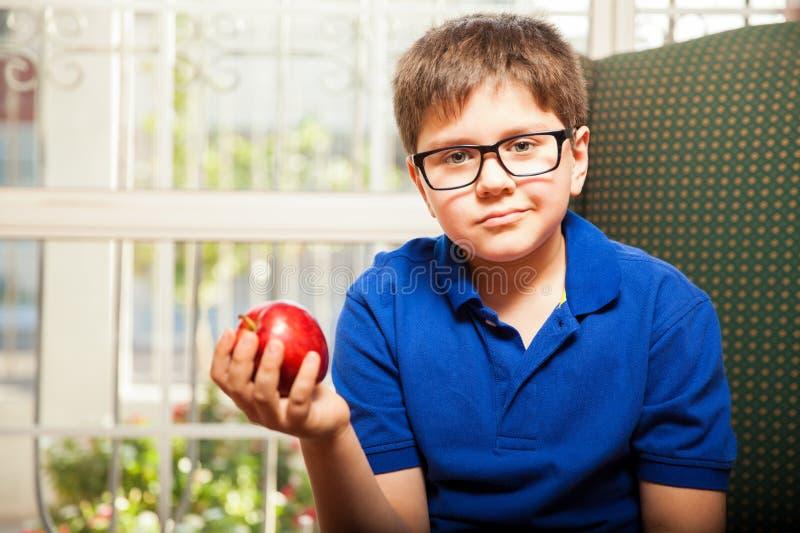 Pojke som rymmer ett äpple i hans hand arkivfoto