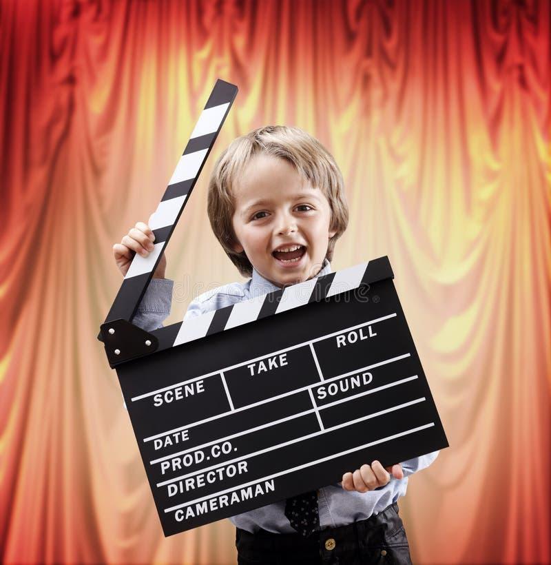 Pojke som rymmer ett clapperbräde i en bioteater arkivfoton