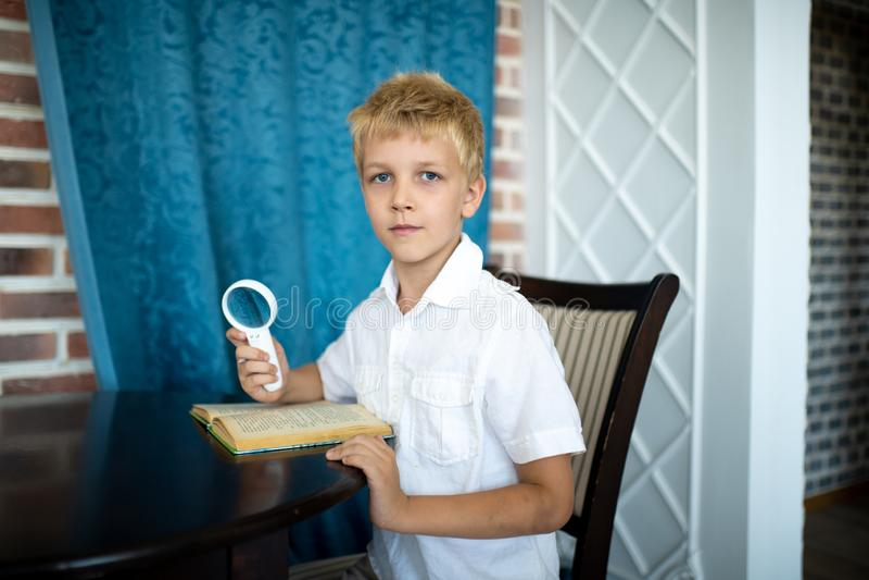 Pojke som rymmer ett förstoringsglas royaltyfria bilder
