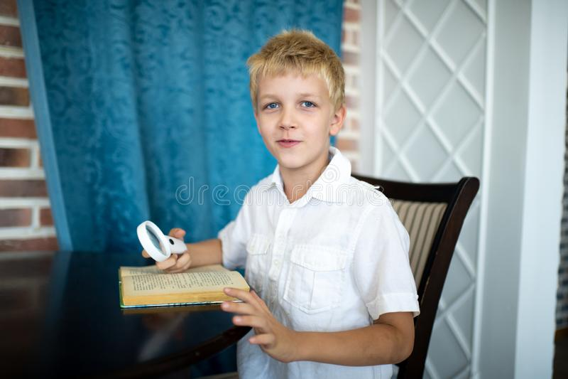 Pojke som rymmer ett förstoringsglas arkivbilder