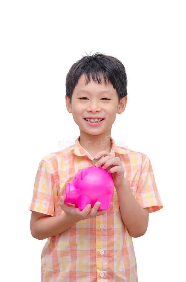 Pojke som sätter in myntet in i spargrisen fotografering för bildbyråer