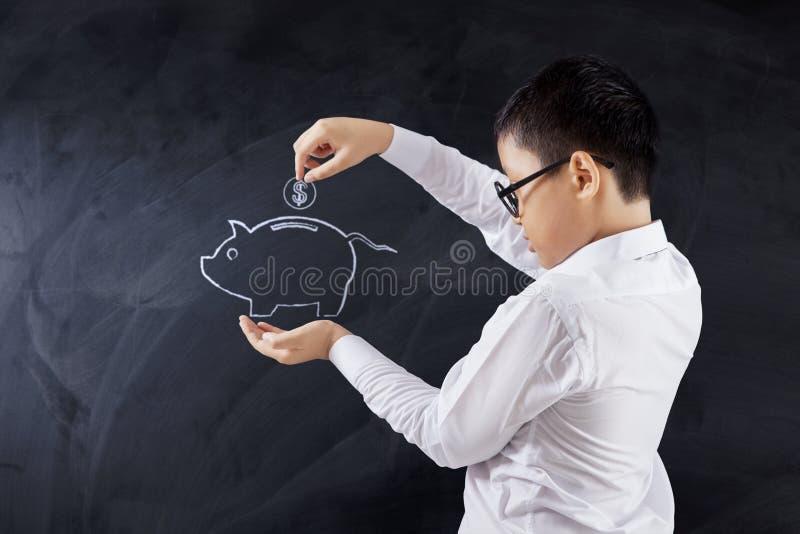 Pojke som sätter myntet in i spargrisen arkivbilder