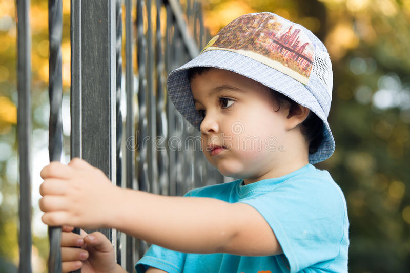 Pojke som ser över staketet arkivfoto