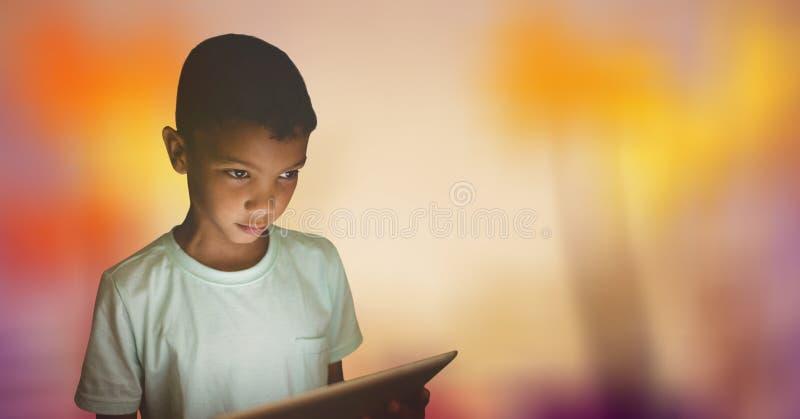 Pojke som ser bort, medan rymma den digitala minnestavlan över bokeh royaltyfri fotografi