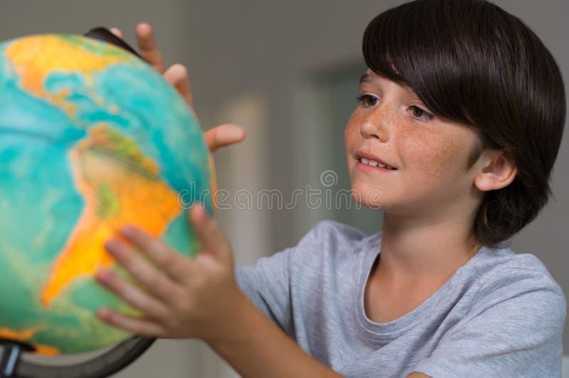 Pojke som ser jordklotet av jord royaltyfri foto