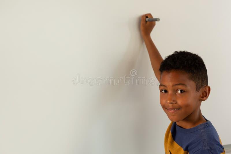 Pojke som ser kameran, medan skriva på en vit vägg royaltyfri bild