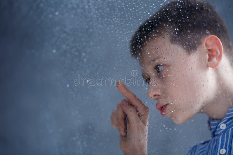 Pojke som ser regndroppar royaltyfria foton