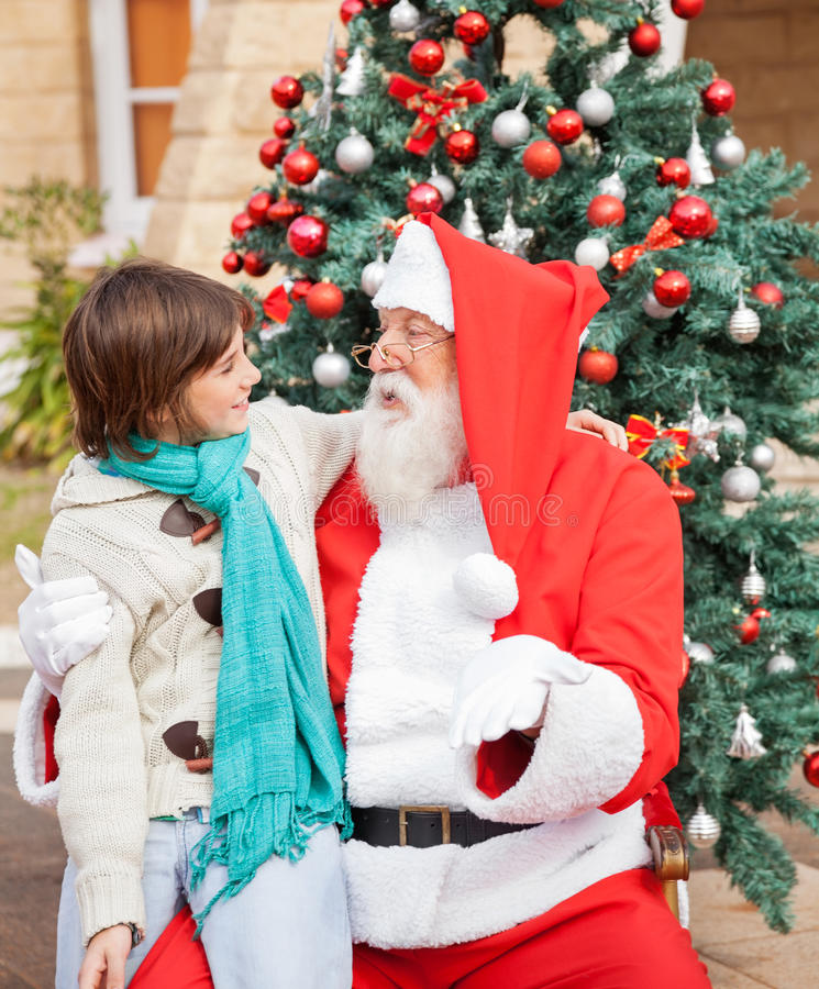 Pojke som ser Santa Claus In Front Of Christmas arkivbild