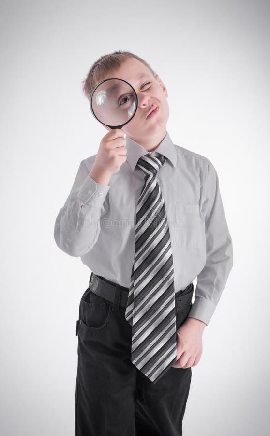 Pojke som ser till och med ett förstoringsglas royaltyfria bilder