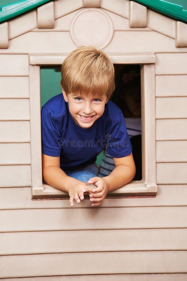 Pojke som ser till och med fönster i lekstuga royaltyfria foton