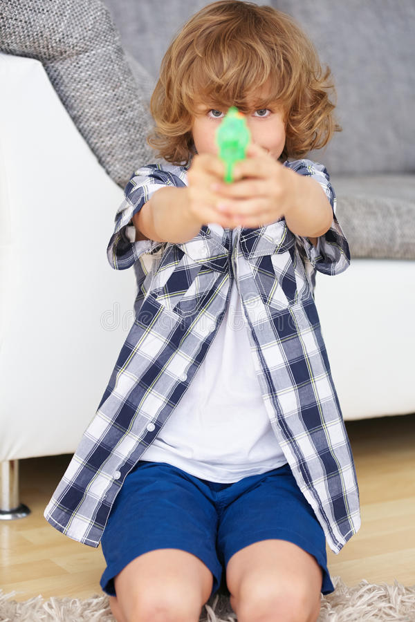 Pojke som siktar med leksakvapnet royaltyfria foton