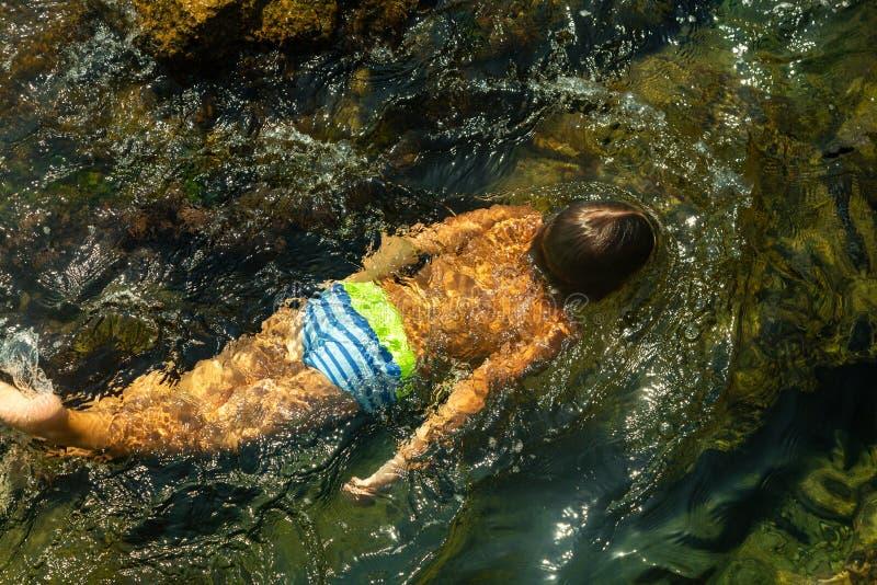 Pojke som simmar undervattens- härlig sikt av kristallklart genomskinligt vatten av havet arkivbilder