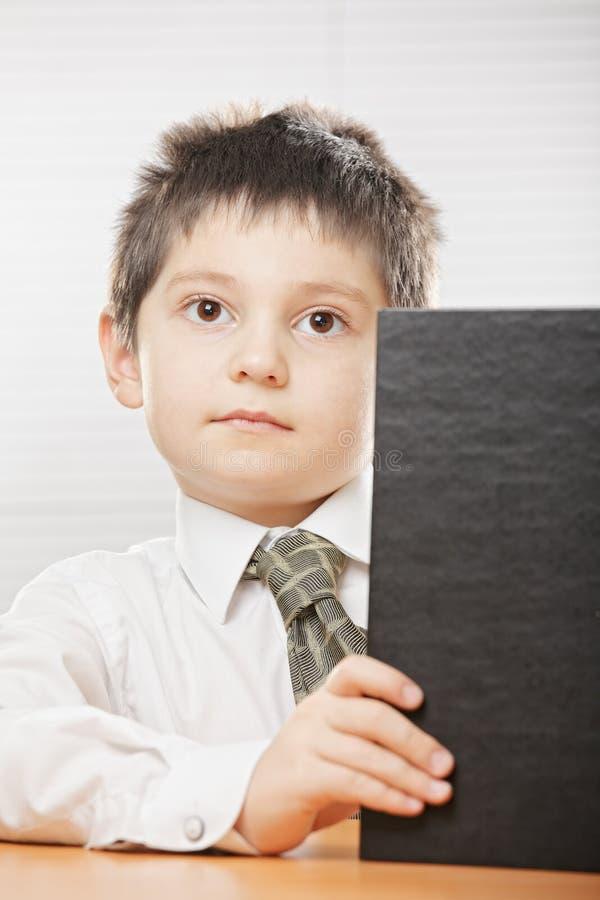 Pojke som sitter bak boken arkivfoto