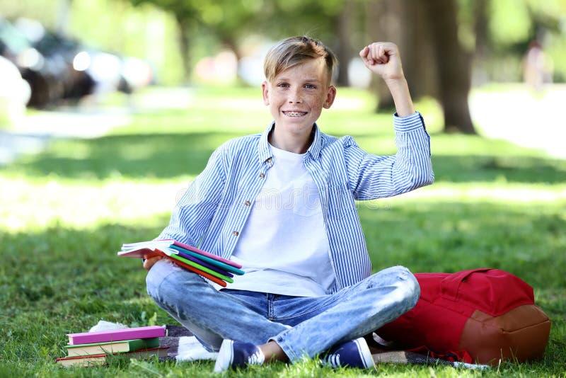 Pojke som sitter med anteckningsboken arkivbild