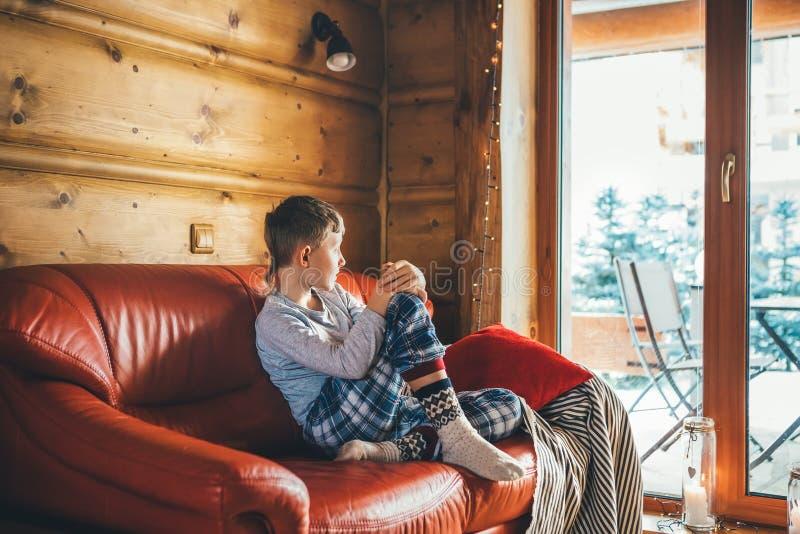 Pojke som sitter på den hemtrevliga soffan på vardagsrum och håller ögonen på i brett fönster i hemtrevlig hem- atmosfär Fridsamm arkivbilder