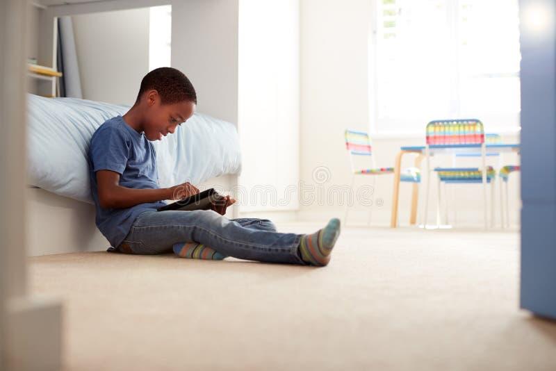 Pojke som sitter på golv i sovrum genom att använda den Digital minnestavlan arkivfoton
