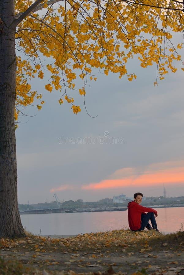 Pojke som sitter på solnedgången royaltyfri bild
