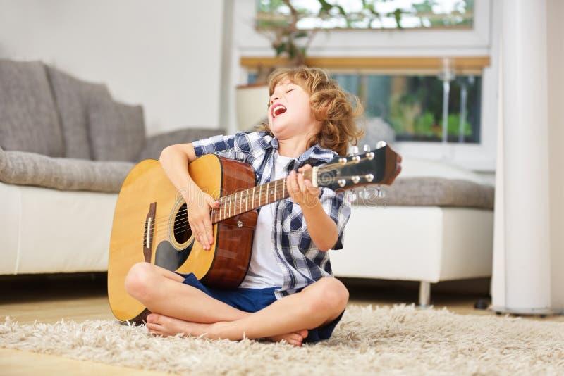 Pojke som sjunger och spelar gitarren royaltyfri bild