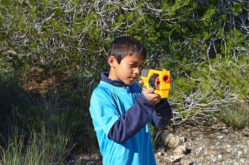 Pojke som skjuter en Toy Gun fotografering för bildbyråer