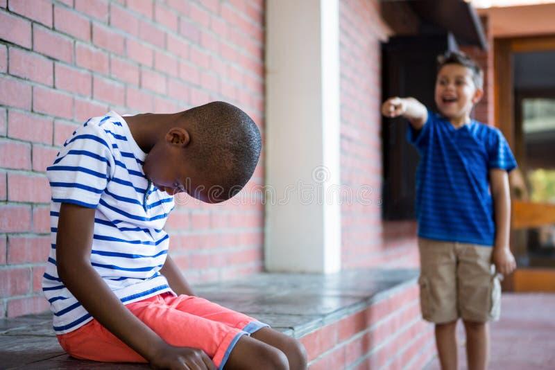 Pojke som skrattar på ledsen klasskompis i korridor royaltyfri fotografi