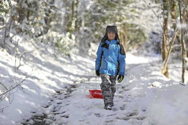 Pojke som sledding ut i snön royaltyfri foto